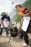 Polenta ball. Two shepherds making a big polenta in two cauldrons stock images
