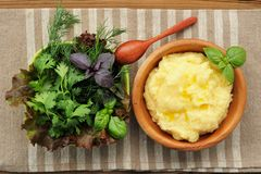 Polenta with basil shoot in wooden bowl with green salad and woo Stock Photo