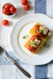 Polenta con i pomodori ed il formaggio Fotografia Stock