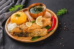 Polenta delicioso con los pescados del prendedero, el queso y la salsa asados a la parrilla de la especia en tabla de cortar sobr foto de archivo