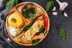 Polenta delicioso con los pescados del prendedero, el queso y la salsa asados a la parrilla de la especia en tabla de cortar sobr fotos de archivo libres de regalías