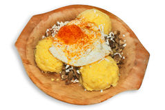 Polenta dish. Polenta balls with mushrooms and egg, served on a wooden plate Stock Photo