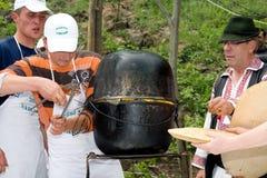 Polenta. Few shepherds making a big polenta in two cauldrons stock images