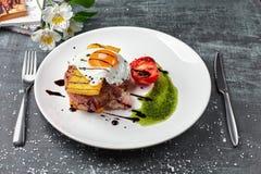 Polenta, homin mit Fleischsteakschweinefleisch und Spiegeleier Hochzeitsabendessen mit Rollenfleisch rauchte und Tomaten Freier P stockbild