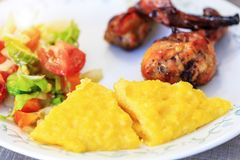 Polenta or Mamaliga, baked chicken legs and salad in fancy plate. Traditional food and culinary culture specific for Balkan royalty free stock photo
