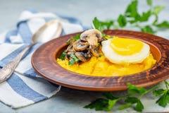Polenta med det caramelized champinjoner, ägget och persilja arkivbilder