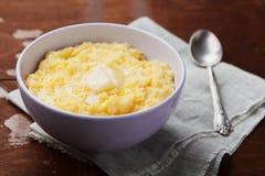 Polenta med smör och ost i platta på den lantliga tabellen royaltyfri fotografi