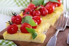 Polenta tart with baked tomatoes Stock Photos