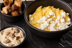 Polenta ucraniano típico del plato - Banosh con queso y manteca de cerdo Cocina ucraniana gachas de avena del maíz con el tocino, imagenes de archivo