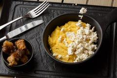Polenta ucraniano típico del plato - Banosh con queso y manteca de cerdo Cocina ucraniana gachas de avena del maíz con el tocino, imágenes de archivo libres de regalías