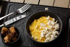 Polenta ucraniano típico del plato - Banosh con queso y manteca de cerdo Cocina ucraniana gachas de avena del maíz con el tocino, foto de archivo