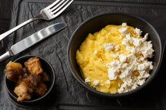 Polenta ucraniano típico del plato - Banosh con queso y manteca de cerdo Cocina ucraniana gachas de avena del maíz con el tocino, fotografía de archivo libre de regalías