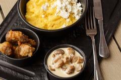 Polenta ucraniano típico del plato - Banosh con queso y manteca de cerdo Cocina ucraniana gachas de avena del maíz con el tocino, fotos de archivo