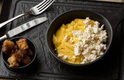 Polenta ucraniano típico del plato - Banosh con queso y manteca de cerdo Cocina ucraniana gachas de avena del maíz con el tocino, fotografía de archivo