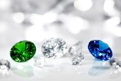 Polerade juvlar, diamant, blå safir och grön smaragd, briljant snitt arkivfoto