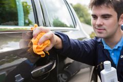 Polerande bildörr för man under bilbetjänt royaltyfri foto