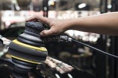 Polerande serie för bil: Arbetare som vaxar blackebilen Royaltyfri Fotografi