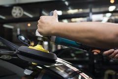 Polerande serie för bil: Arbetare som vaxar blackebilen Royaltyfri Foto