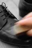 Polerande skor för man med en borste arkivbild