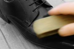 Polerande skor för man med en borste fotografering för bildbyråer