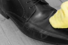 Polerande skor för man med en torkduk arkivfoto
