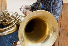 Polering av en tuba Arkivfoto