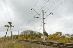 The poles with the electric current along the railway. The poles along the railway.Through wire is electric current Stock Photography
