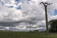 Poles with electric lead in the meadow before the storm. In Czech Republic Stock Photo