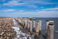Poles beside ocean with stones put on top. In Provence, near Camargue, France the ocean line is fileld with miles of poles on the ocean coast with stones Stock Photo