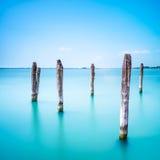Poles och mjukt vatten på den Venedig lagun. Lång exponering. Royaltyfri Foto