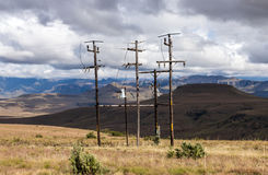 Poles and Overhead Powerlines Against Mountain Landscape Royalty Free Stock Images