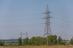 The poles of a power line against a blue sky high voltage power Royalty Free Stock Photography