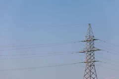 The poles of a power line against a blue sky high voltage power Royalty Free Stock Image