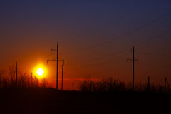 Poles of power lines at sunset - industrial landscape Royalty Free Stock Photos