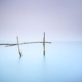 Poles and soft water on foggy landscape. Long exposure. Stock Photography