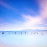 Poles and soft water on sea landscape. Long exposure. Stock Images