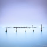 Poles and soft water on water landscape. Long exposure. Royalty Free Stock Photography