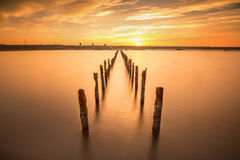 Poles in the water -  on sunset clouds and ocean Royalty Free Stock Images