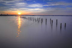 Poles in the water -  on sunset clouds and ocean Stock Photography