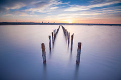 Poles in the water -  on sunset clouds and ocean. Poles in the water, on sunset clouds and ocean- calmness and silence concept Stock Photography