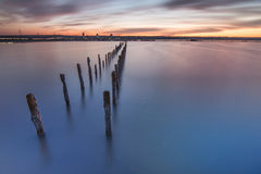 Poles in the water -  on sunset clouds and ocean Royalty Free Stock Image