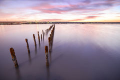 Poles in the water -  on sunset clouds and ocean Stock Images