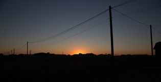Poles with wires at sunset Stock Photos