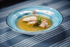 Polewka w błękita talerzu z kurczaka rosołem, kurczaka ` s nogą, kluchami i greenery, Talerz na stole z błękitnym tablecloth zdjęcia stock