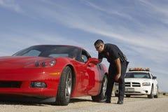 Poli de tráfico que para el coche de deportes rojo Imagenes de archivo