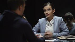 Poli serio de la señora que da los papeles de la culpabilidad de la confesión al hombre para la muestra, solucionando crimen almacen de metraje de vídeo