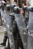 Policía antidisturbios detrás de los escudos en Ecuador Imagen de archivo