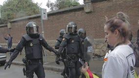 Policía antidisturbios española que baja, seguido por los manifestantes catalanes metrajes