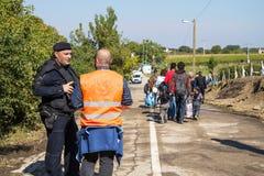 Policía croata y NGO Volunteer que miran a los nómadas que cruzan la frontera de Serbia Croacia en Berkasovo Bapska fotos de archivo