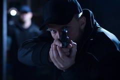 Policía que apunta el arma durante la intervención Imágenes de archivo libres de regalías